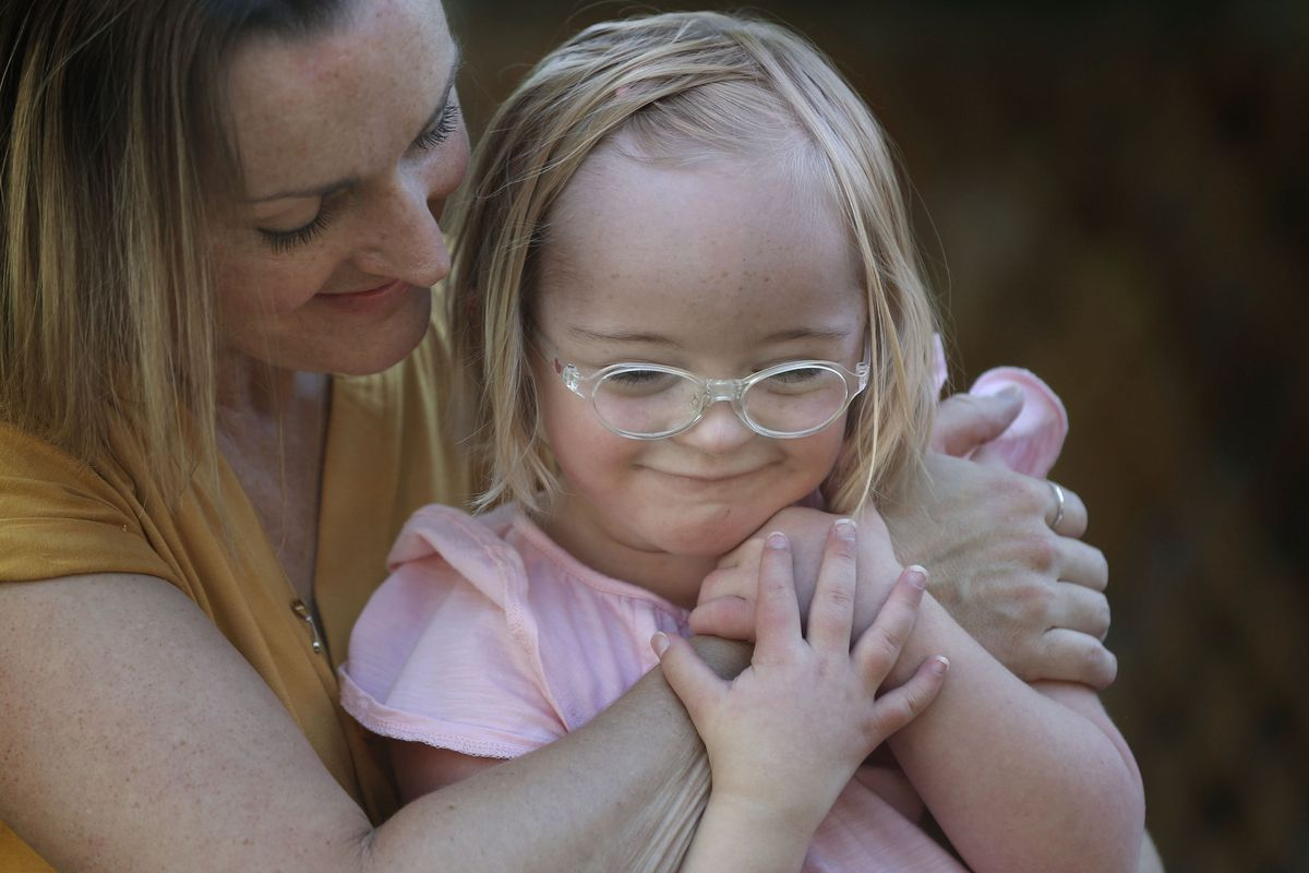 Amanda Longwell hugs her daughter, Tori, who will be a first grader at Highland Park Elementary School, at their home in Salt Lake City on Wednesday, July 29, 2020. The Longwells have decided as a family to return to remote learning this fall due to risks to Tori, who has Down syndrome, but also to the entire family.