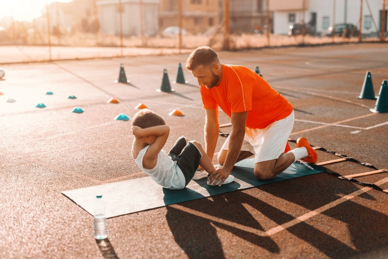 Kid working with personal trainer