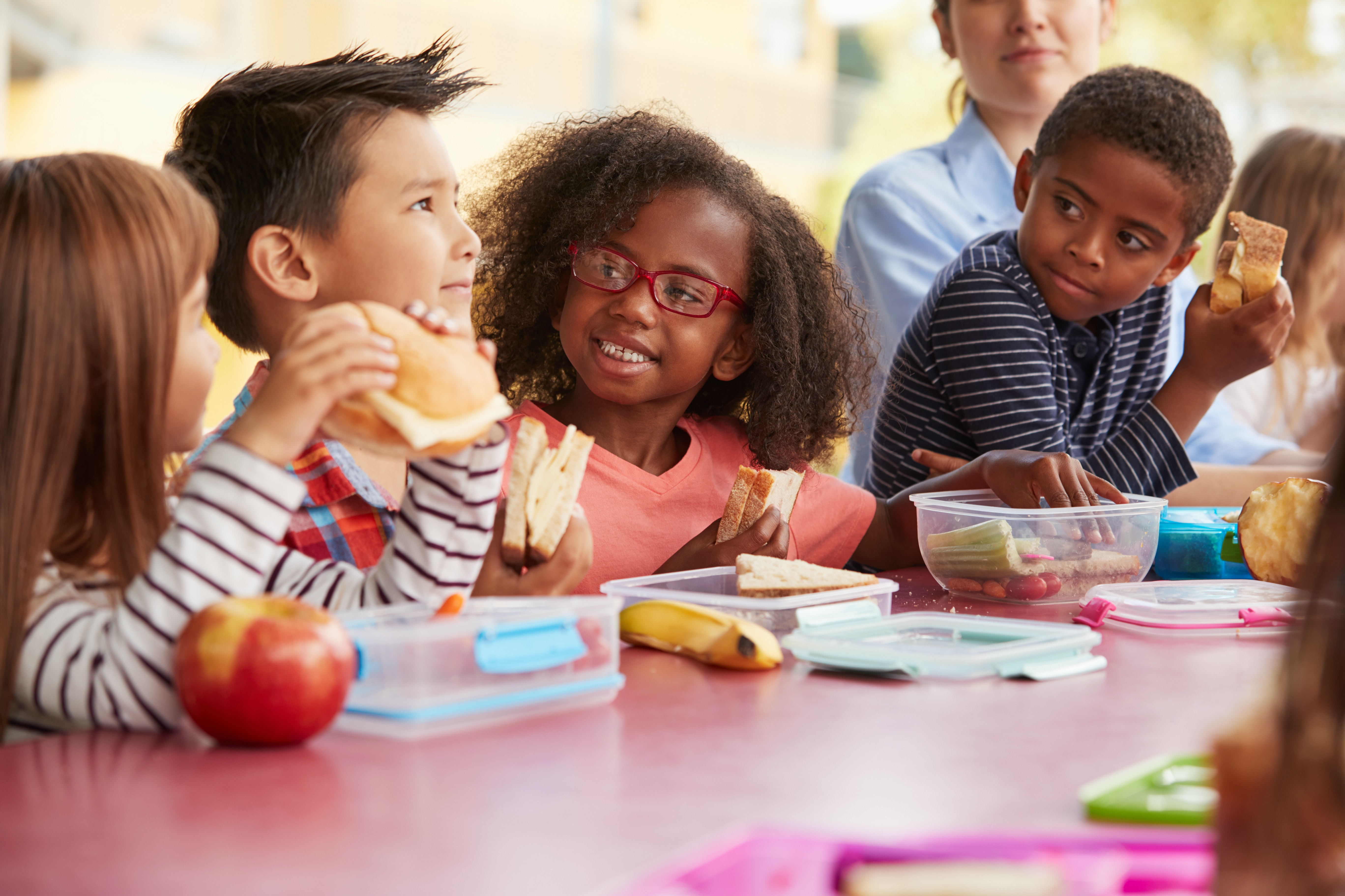 Children talking and eating packed lunches at a table
