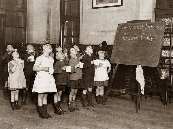 Children in England, circa 1935, gargling as a precaution against the influenza epidemic.