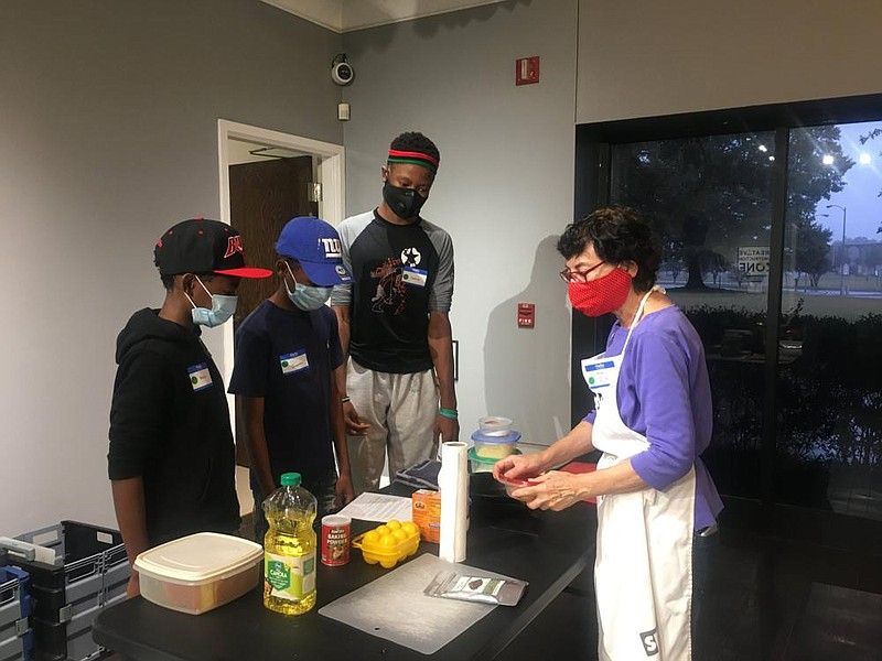 CrEATe Lab cooking workshop instructor and cooking expert Faith Anaya (right) introduces the Adams brothers, Cedric (right), Quentin (center) and Mekhi (left) to skillet cornbread. (Special to The Commercial/Deborah Horn)